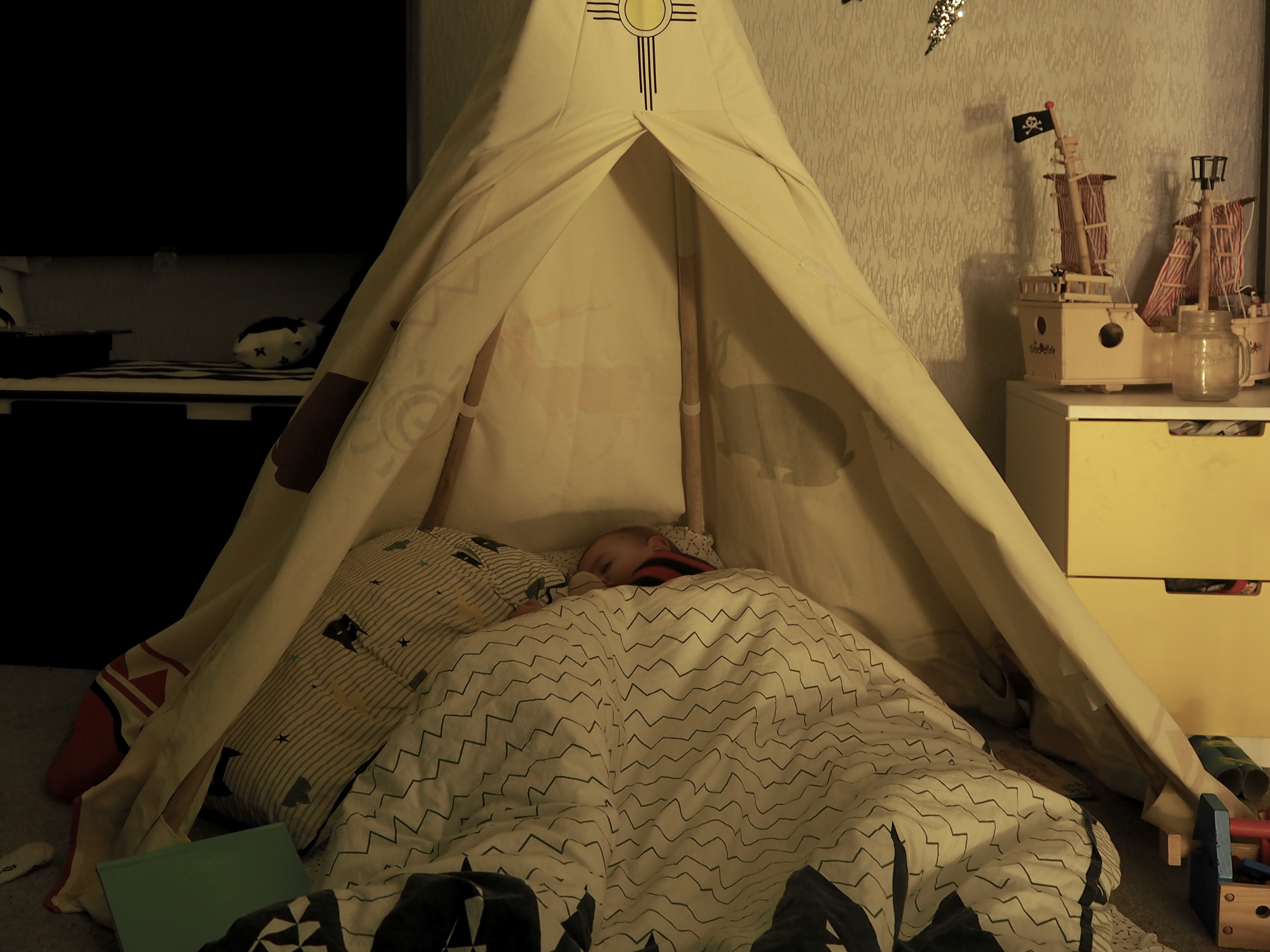 Toddler sleeping in a teepee