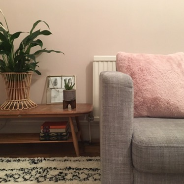 Grey settee with fluffy pink cushion against pink wall, with an Ercol coffee table